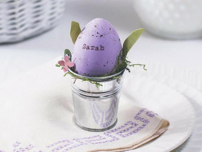 the name sarah, written on a spotty purple egg, placed inside a small metal bucket, decorated with paper flowers and leaves, easter egg decorating, plate with napkin