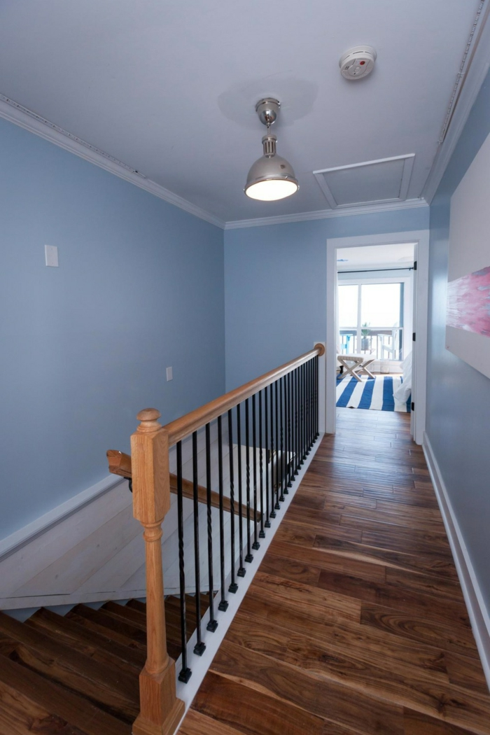 landing with pale pastel blue walls, and white ceiling with a plain light, wooden floors and banisters, hallway decor, framed painting with white and pink