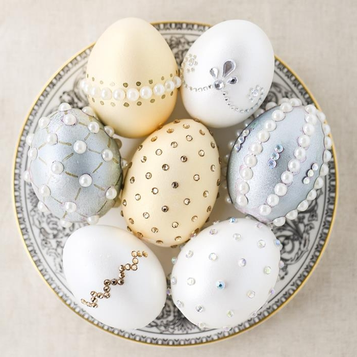 pale peach, silver and white eggs, decorated with stick-on white pearls, silver and gold gem stickers, dying easter eggs, inside a white dish, with grey decorations