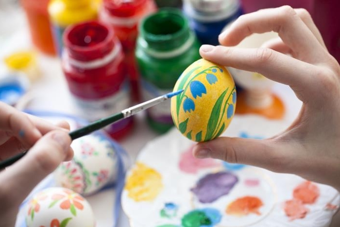 hand holding a painted yellow egg, with blue and green flower, while another hand holds a brush covered in blue near the egg, easter egg designs, paints and palettes in background