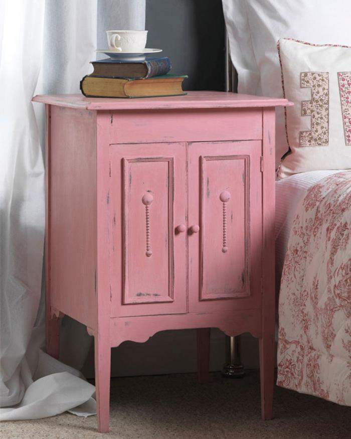 books and a teacup, on pastel pink vintage cabinet, with shabby chic look, near bed with floral covers