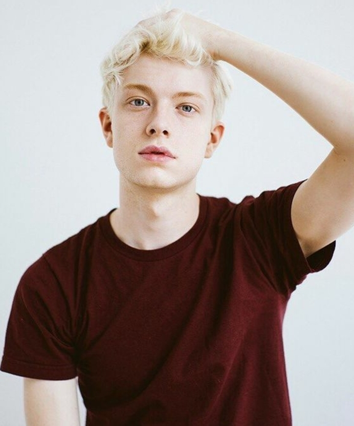 pale youth with blue eyes and short, wavy platinum blonde dyed hair, wine red t-shirt