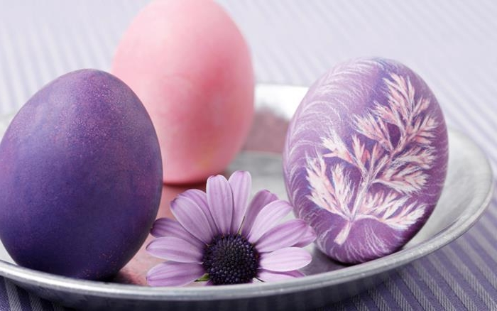 how to dye easter eggs, purple dyed egg, decorated with a crayon drawing of a leaf, in pink and white, placed on a metal plate, near a plain pink and purple egg, and a purple flower