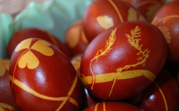 botanical shapes in yellow, printed on red eggs, easter egg coloring the traditional way