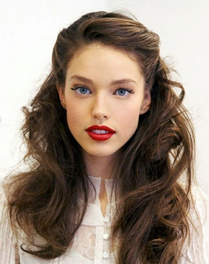 messy and wavy, partially tied back hairstyle, with side-swept, retro-inspired bangs, medium length brown hair, worn by woman in white semi-sheer top, with bright red lipstick, black eyeliner and fake lashes