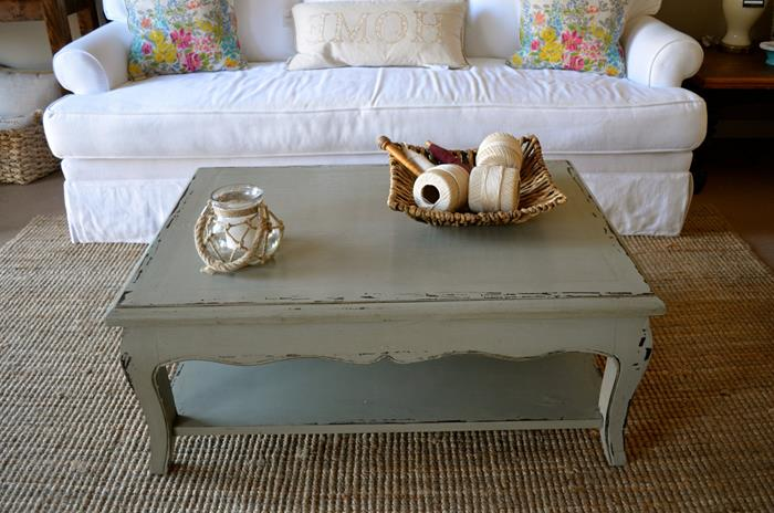 shabby chic sofa in pure white, with two multicolored floral cushions, and a pillow in cream, near grey country chic table, on beige textured rug