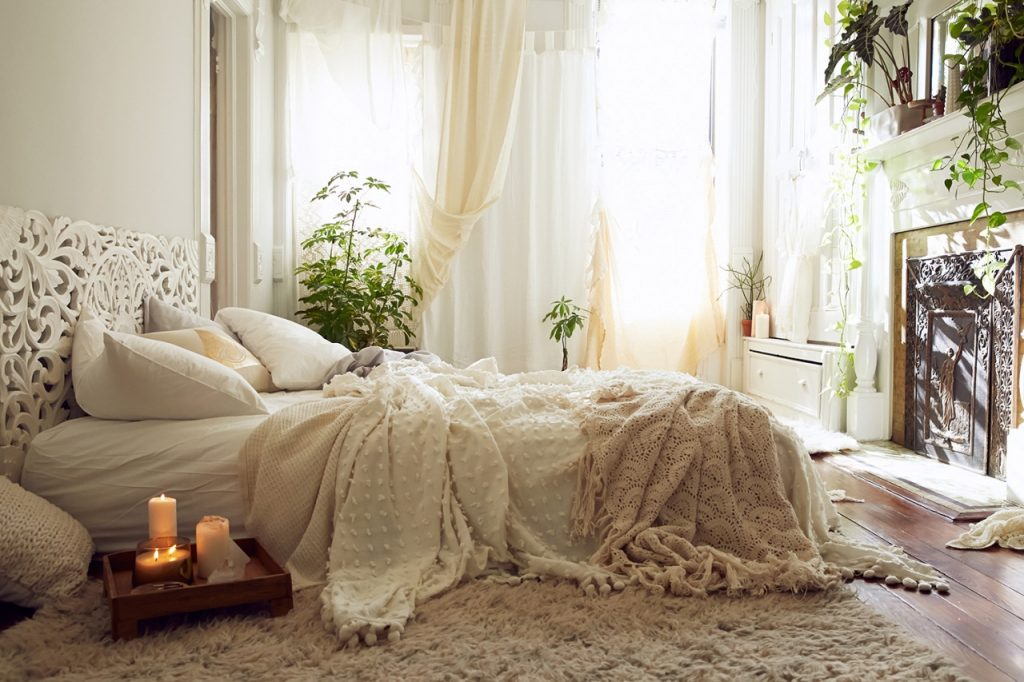 bedroom in white and cream, bed with several blankets pillows and throws, fluffy rug on a wooden floor, tray with lit candles, several different potted plants