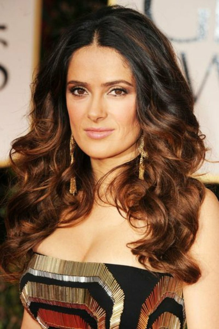 black strapless dress, embroidered with golden, silver and red thread, worn by salma hayek, dark haired actresses, partially curled dark brunette hair, with auburn balayage