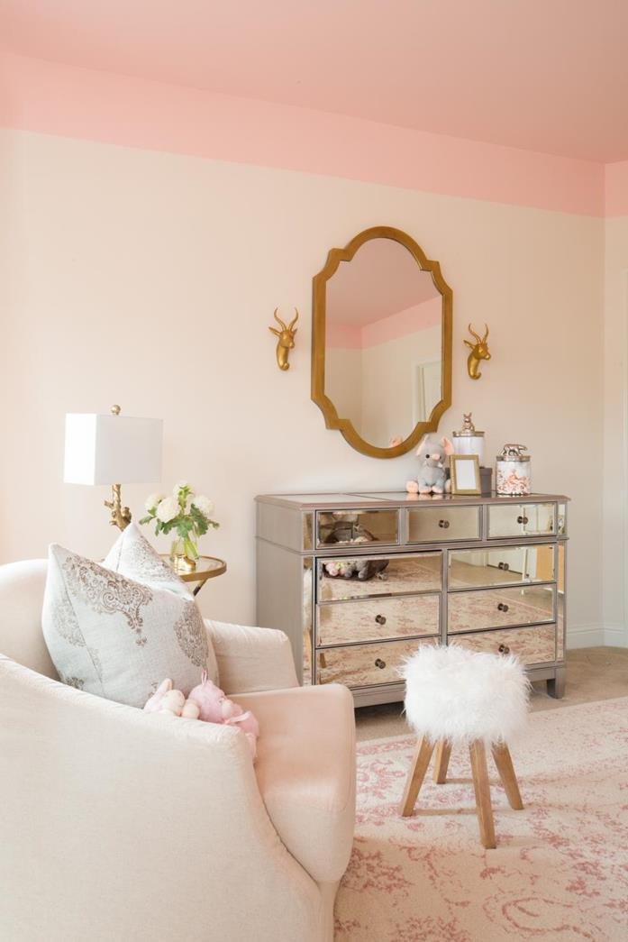 mirror covered cupboard, near cream shabby chic sofa with cushions, wooden stool with white furry top, faded vintage rug, shabby sheek pale pink walls