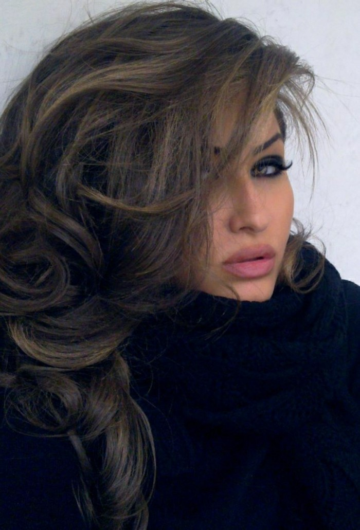 voluminous side swept and layered, brown highlighted hair, with dark blond strands, on woman with pink lipstick, and bold eye make up, with fake eyelashes, and chunky knit black scarf