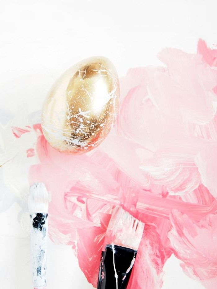 flat paintbrushes covered in pink and white paint, near a golden dyed egg, covered in white splashes of paint, easter egg decorating