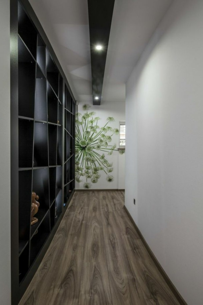 black asymmetrical shelves covering a wall, in corridor with wooden floor, opposite wall is plain white, third wall has a green floral mural, hallway furniture ideas