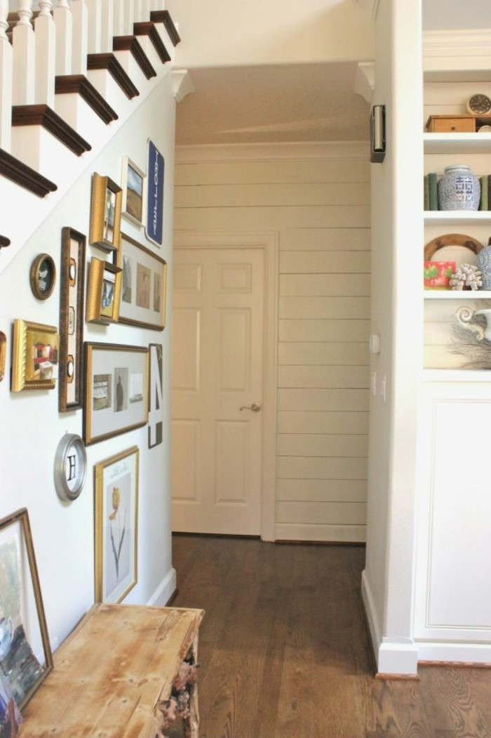 many frames of different shapes and sizes, on a white wall under a staircase, hallway decorating ideas, solid wood floor, white shelves containing various items