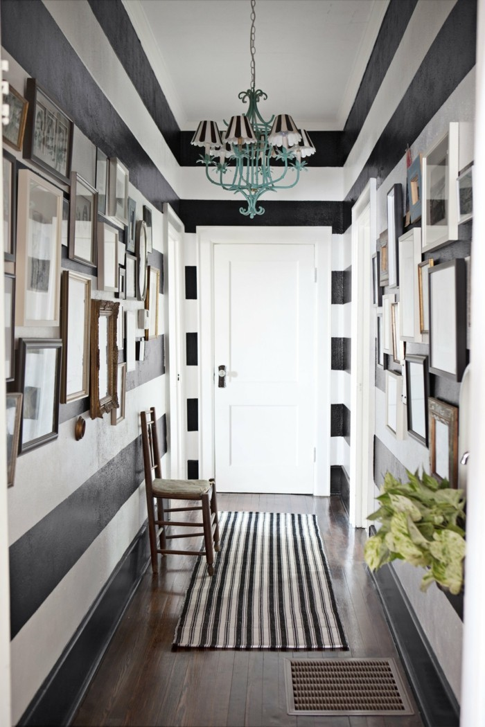 corridor painted in white and black stripes, with many images in different frames, small hallway ideas, dark wooden floor with striped rug, one wooden chair, blue chandelier with several striped lampshades
