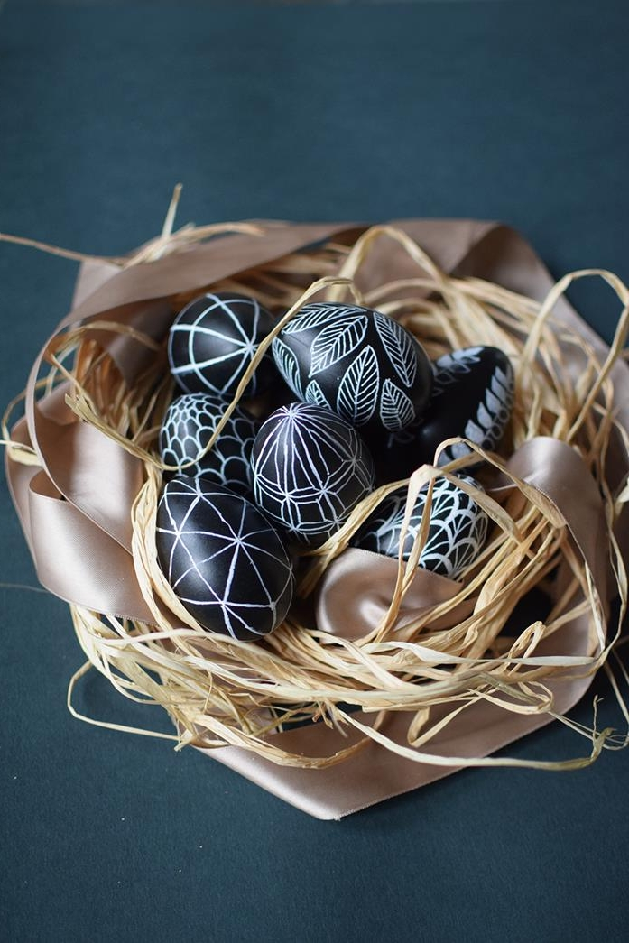 shiny black eggs, decorated with white drawings, of leaves and scales, geometric shapes and other patterns, dying easter eggs, placed in a nest made of straw, and a pale pastel pink ribbon