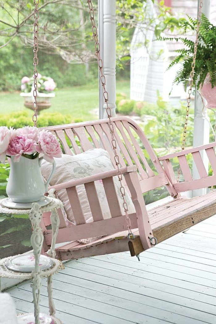 bench swing painted in pastel pink, hanging from pink chains, near a small white antique ornamental table, with a white jug, containing pink peonies
