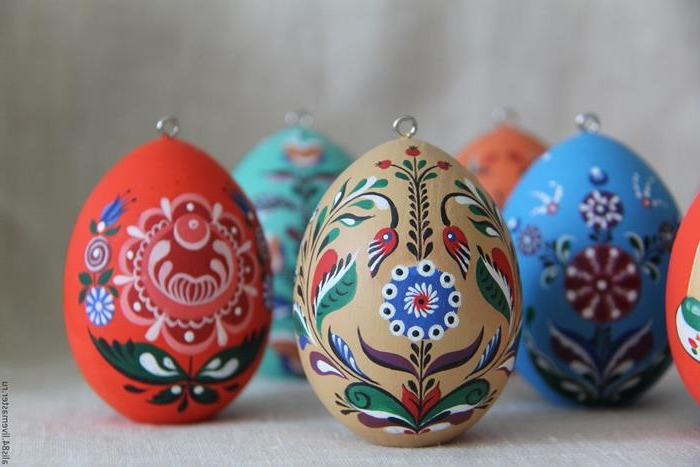 professionally painted easter egg decorations, blue and beige, red and green, with symmetrical floral motifs and patterns, polish or russian