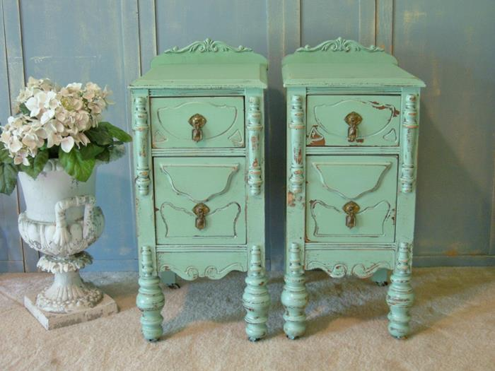 matching small antique cupboards, in mint green, country chic décor, placed on a pale beige carpet, near a vase with white flowers