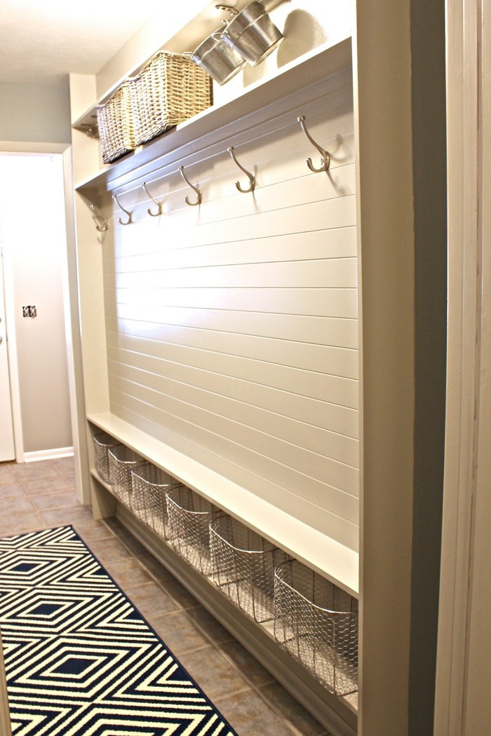 hallway decor ideas, beige tiled floor, black and white patterned rug, near wall covered with white planks, with several coat hangers, and various baskets for storage