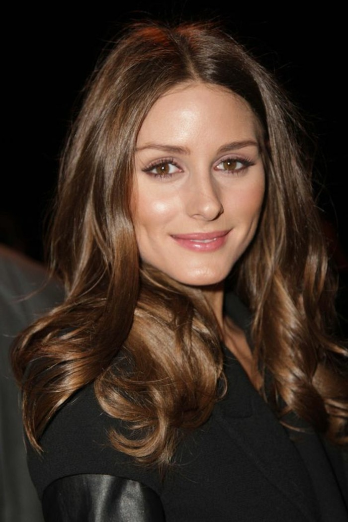 soft wavy tresses, in medium brown hair color, on smiling woman, dressed in black coat with leather trim, discreet make up and dimples