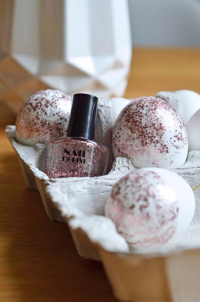 decorating eggs with nail polish, three white eggs, half-covered in clear nail polish, with pink glitter, placed in a cardboard egg box, near the nail polish bottle