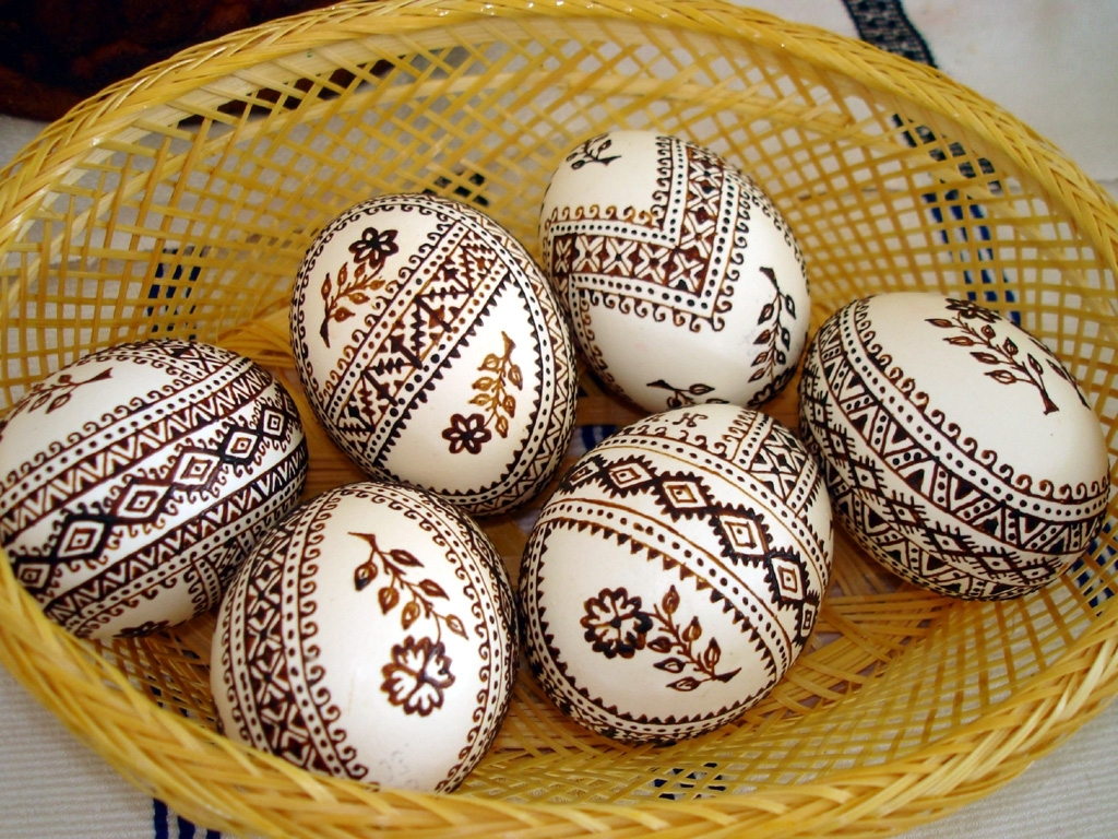 henna drawings with complex patterns on six white eggs, how to dye easter eggs, placed inside a wicker basket