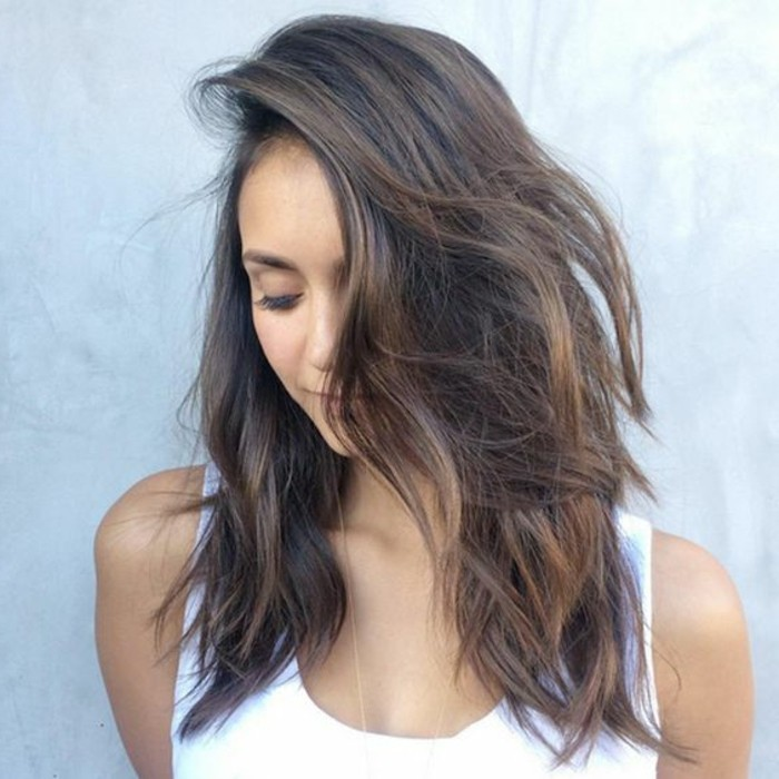 nina dobrev in white tank top, with side swept wavy hair, in medium brown hair color, with dark blonde highlights