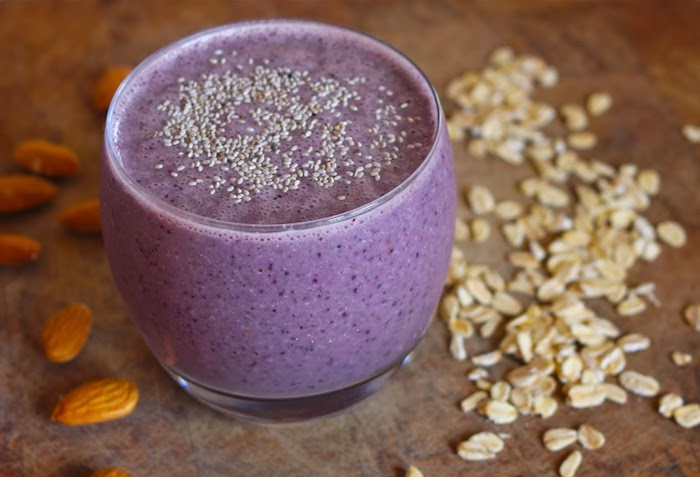 tiny seeds topping a small glass, filled with a blended purple drink, fruit smoothie recipes, raw almonds and oatmeal flakes nearby