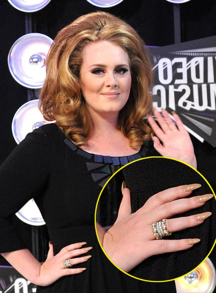 adele with dark blonde, voluminous curled hair, black eyeliner and dress, close-up of her hand reveals long pointy nails, painted in beige nail-polish