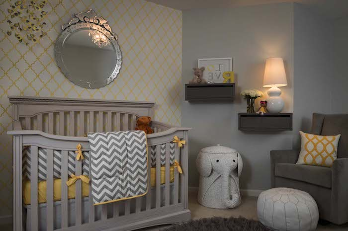 baby nursery, in gray and yellow, with creamy light gray crib, large ornate wall mirror, dark gray armchair, white and yellow cushion, and other yellow details