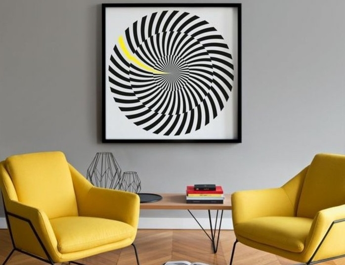 set of two modern yellow armchairs, near minimalistic light wooden table, and large framed artwork, colors that go with gray walls, modern interiors