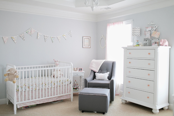 dark gray armchair, and matching footstool, near baby crib in white and pale pink, and matching chest of drawers, baby girl room décor, pale lavender walls, toys and decorations