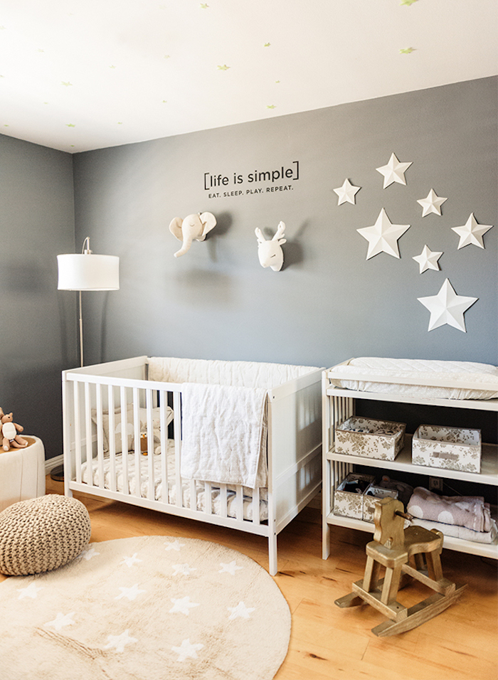 star motifs on gray wall, decorated with black text, and elephant and deer plush heads, near white baby crib, rocking horse chair, and changing table with shelves, baby girl room décor