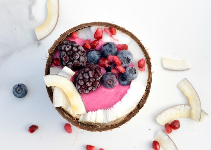 halved coconut filled with fruity, pale pink creamy substance, healthy breakfast smoothies, topped with blackberries, blueberries and pomegranate seeds, coconut chunks nearby