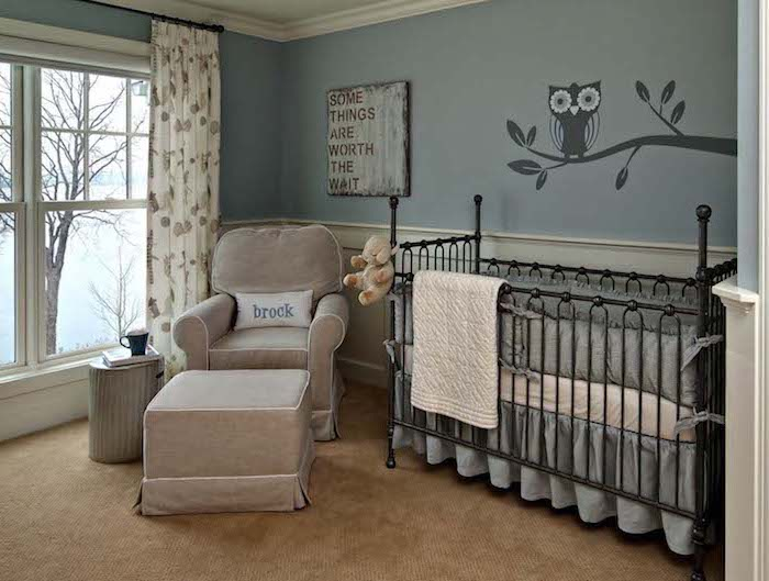 metal ornamental crib in black, with gray and white bedding, near beige armchair, with matching foot stool, in baby nursery, with pale blue walls, white paneling and small dark gray mural
