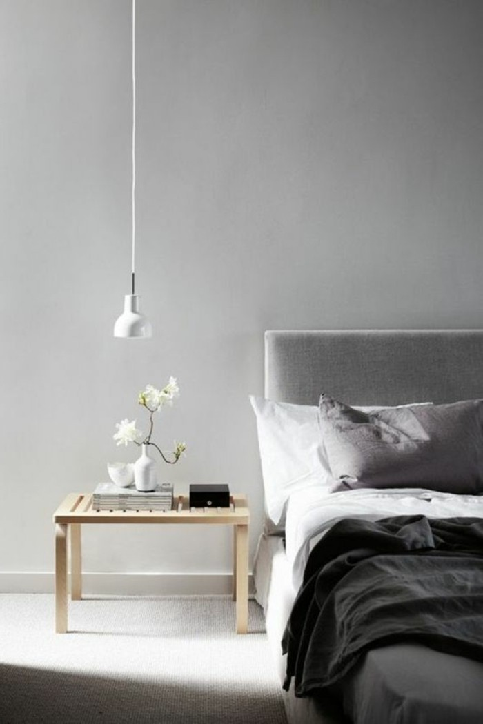 minimalist bedroom, with light gray walls, small wooden bedside table, grey bed with white, light and dark gray bedcovers