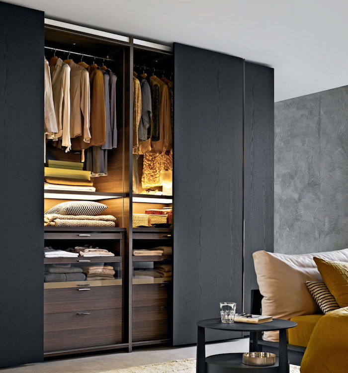 open closet with sliding doors, made of black wood, with clothes and blankets, near bed with black bedside table