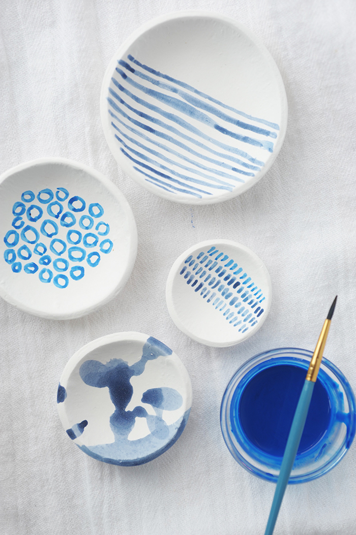 four white plates, decorated with light blue patterns, done in watercolor, mothers day gifts, glass with blue paint, and brush nearby