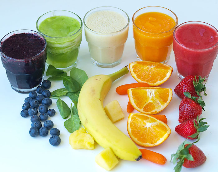 strawberries and oranges, baby carrots and a banana, spinach and blueberries, near five glasses, containing frothy blended drinks, spinach smoothie ideas