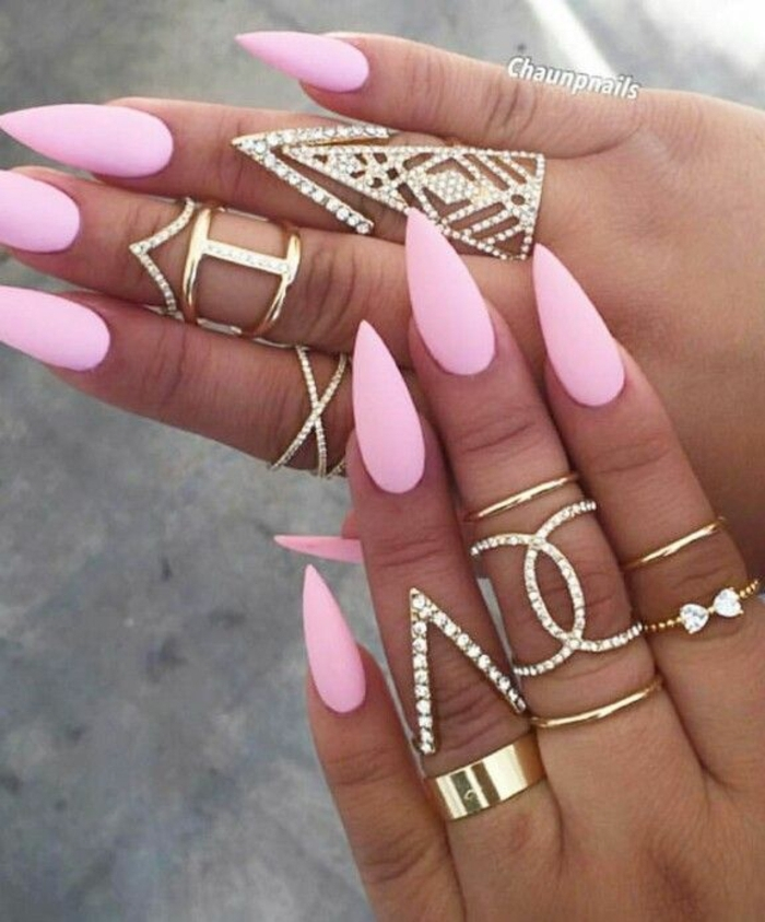 chunky golden rings, some decorated with rhinestones, on two hands, with long manicure, painted in light matte pink nail polish
