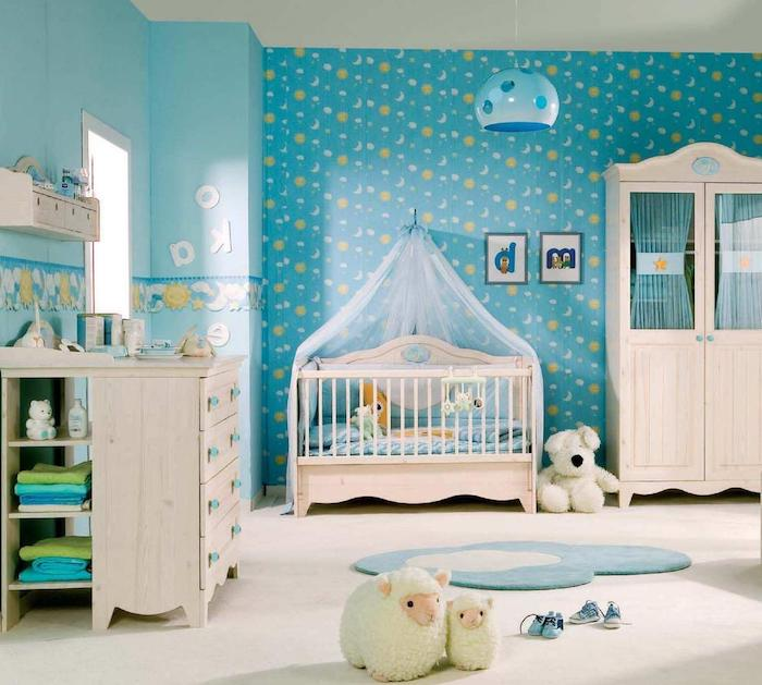wallpaper in blue, with sun and moon pattern, in boy nursery, with pale beige wooden furniture, clothes and stuffed toys