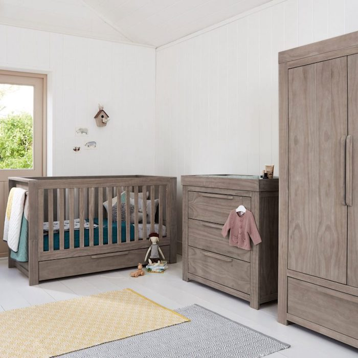 furniture for a nursery, a set of brown baby crib, wardrobe and changing table, baby girl room décor, in white room, with toys and clothes