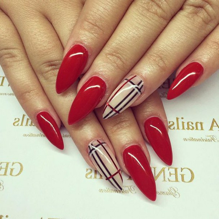 stiletto nails, painted in smooth and bright, shiny red nail polish, accent nails decorated with black, white and red stripes, inspired by burberry