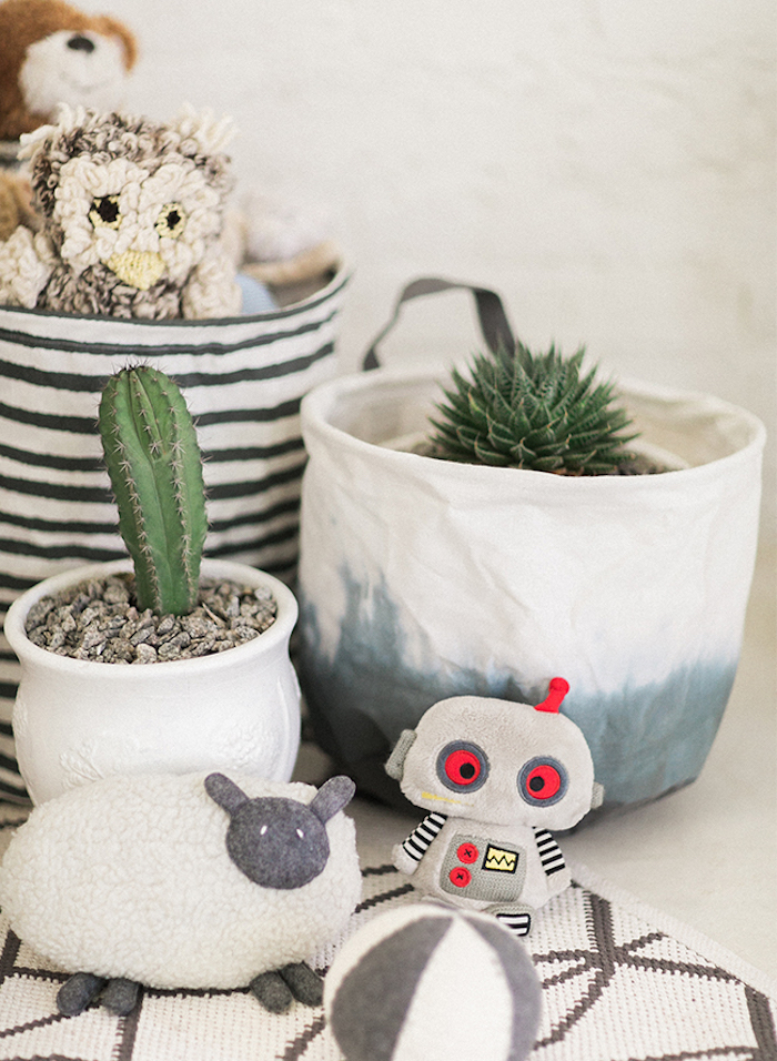 two indoor plants, in ceramic pots, cactus and succulent, bag with stuffed toys, gender neutral nursery, stuffed sheep robot and ball, patterned rug in white and beige