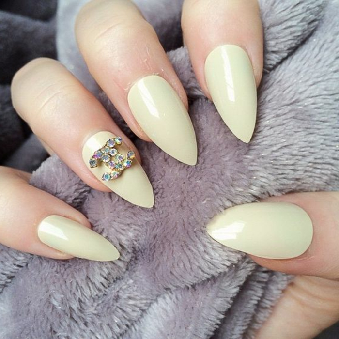 yellowish-green nail color, on sharp pointy manicure, one nail is decorated with chanel logo, covered in iridescent rhinestones