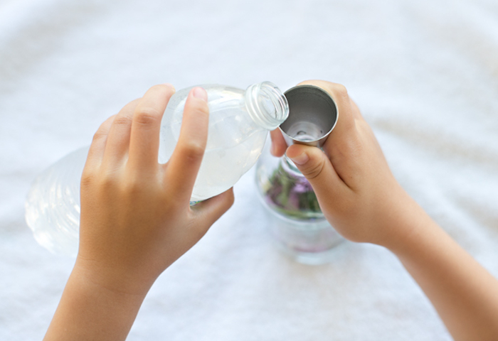 small child hand, pouring water from plastic bottle, into clear bottle with flowers, using metal funnel, mother's day gift ideas, fun diy project