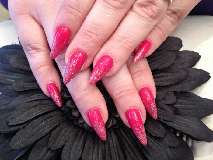 narrow and sharp claw nails, painted in red nail polish, and decorated with subtle silver glitter, on two hands, resting on black artificial flower