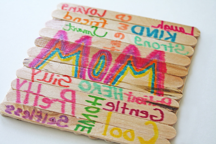 wooden ice-cream sticks, stuck together to form a coaster, decorated with greetings for mom, written with markers in different colors