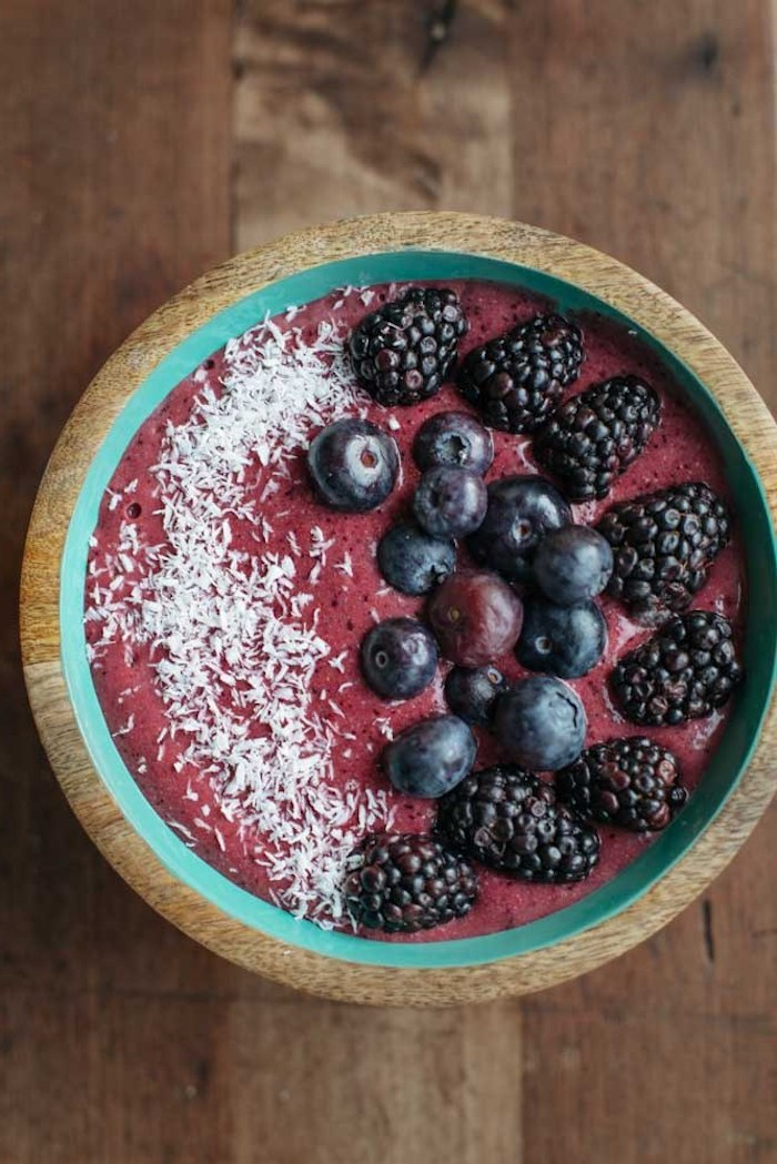 puree made from berries, inside a wooden turquoise bowl, healthy breakfast smoothies, topped with whole blueberries and blackberries, and a dusting of coconut shavings