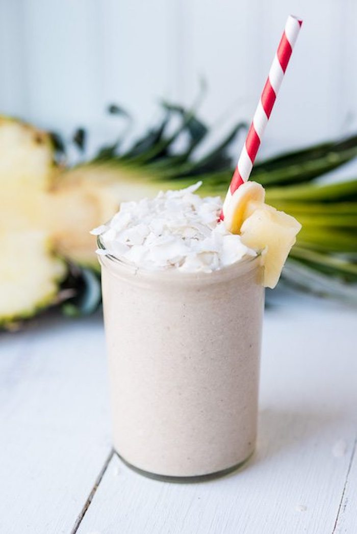 plain clear glass, filled with beige creamy drink, topped with coconut flakes, banana and pineapple chunks, fruit smoothie recipes, halved pineapple in the background
